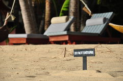 Undisturbed vacation. Do not disturb sign in front of two empty beach beds on Mae Nam beach on Koh Samui in Thailand stock photography