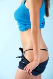 Undress profile. Young woman poses taking off her shorts Royalty Free Stock Image
