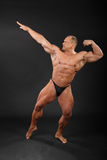 Undressed bodybuilder aiming for punch Stock Photos