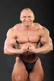 Undressed bodybuilder demonstrates arm muscles Royalty Free Stock Photo