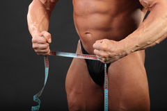Undressed bodybuilder holds measuring tape Royalty Free Stock Image