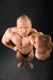 Undressed bodybuilder punches to camera Stock Photos