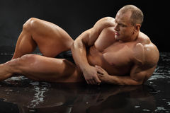 Undressed bodybuilder in rain lies on wet floor Royalty Free Stock Photography
