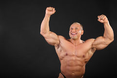Undressed bodybuilder raises fists up Stock Photo