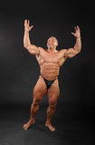 Undressed bodybuilder raises hands up Royalty Free Stock Photography
