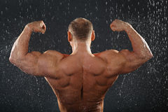 Undressed bodybuilder stands in rain Royalty Free Stock Image