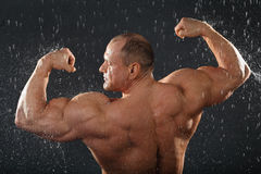 Undressed bodybuilder stands in rain Royalty Free Stock Photos