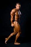 Undressed garvade kroppsbyggare visar hans beväpnar och lägger benen på ryggen musc royaltyfri fotografi