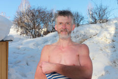 The undressed man in the winter. The mature undressed man takes air baths outdoors among snow in the winter Royalty Free Stock Photos