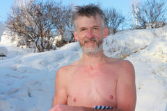 The undressed man in the winter. The mature undressed man takes air baths outdoors among snow in the winter Stock Photography