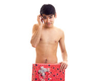 Undressed young man holding present. Young smart-looking man with dark hair standing undressed and holding red present on white background in studio Royalty Free Stock Image