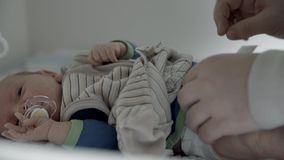 Undressing baby. Mother changing her baby's diaper stock video footage