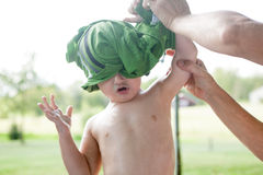 Undressing: Taking off Shirt. Child taking off his shirt outside. He is being helped by his mother Royalty Free Stock Image