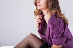 Undressing woman in bedroom Stock Image