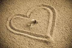 Undying Love. With Wedding Band In Sand Heart Royalty Free Stock Photos
