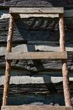 Une échelle faite maison se penche contre un mur de carlingue de rondin photos stock