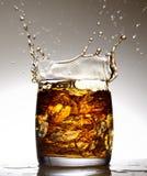 Une éclaboussure délicieuse dans un verre de whiskey et de glace sur un fond noir images libres de droits