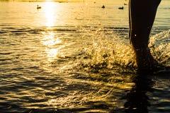 Une éclaboussure de l'eau créée par le pied du ` s de garçon, la trace orange du soleil étouffant Photographie stock libre de droits