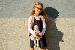 Une écolière mignonne d'école primaire sourit avec un jouet dans elle Photographie stock libre de droits