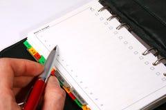 Une écriture de main dans un organisateur vert avec un crayon lecteur rouge Photos stock