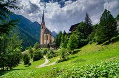Une église se repose parmi le terrain montagneux dans Heiligenblut, Autriche photos stock