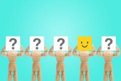 Une émotion en bois de visage de participation de figure dans le bonheur et d'autres figures tenant le point d'interrogation à di photo libre de droits