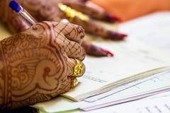 Une épouse bengali indienne nouvellement mariée avec la fiche de signature de mariage d'anneau de mariage d'or Image stock