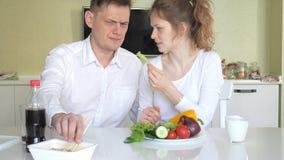Une épouse et un mari s'assied à une table mangeant les nouilles chinoises et les légumes frais Le concept de la nutrition approp banque de vidéos