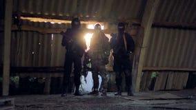 Une équipe de choc se repose avec leurs armes automatiques dans des mains clips vidéos