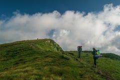 Une équipe de deux touristes s'élèvent jusqu'au dessus de la montagne photographie stock