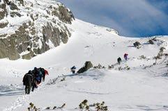 Une équipe escaladant une montagne Image libre de droits