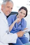 Une équipe médicale de sourire regardant un document photos libres de droits