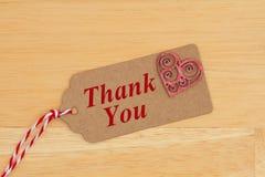 Une étiquette de cadeau avec un coeur rouge d'étincelle et le texte vous remercient images libres de droits