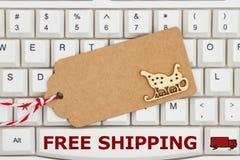 Une étiquette de cadeau sur un clavier avec l'expédition libre des textes photo libre de droits