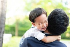 Une étreinte de fils son père et sourire avec le costume occasionnel en parc images libres de droits