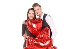 Une étreinte heureuse affectueuse de couples parmi les multitudes de boules rouges d'hélium D'isolement sur le fond blanc Images libres de droits