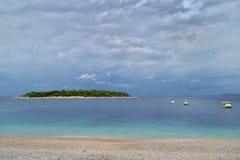Une île verte en mer azurée Plage, bateaux et ciel nuageux photo libre de droits