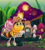 Une abeille de vol près de la maison enchantée de champignon Photographie stock