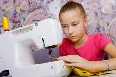 Une adolescente apprend à coudre image stock