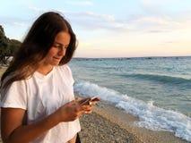 Une adolescente avec un téléphone portable sur la plage avec la lumière de coucher du soleil Images libres de droits
