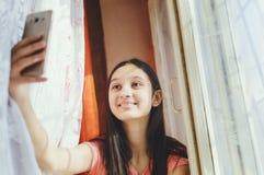 Une adolescente fait le selfie à un téléphone portable photos libres de droits