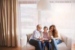 Une adolescente, une mère et une grand-mère avec le comprimé à la maison Image stock