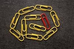 Une agrafe rouge parmi le jaune ceux Images libres de droits