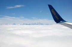 Une aile d'avions au-dessus des nuages Photographie stock libre de droits