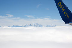 Une aile d'avions au-dessus des nuages Photographie stock