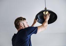 Une ampoule changeante d'homme occidental Photos stock