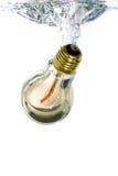 Une ampoule tombant dans l'eau photographie stock libre de droits