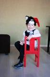 Un enfant drôle a vêtu d'un costumé d'un chat dans une chambre Photographie stock libre de droits