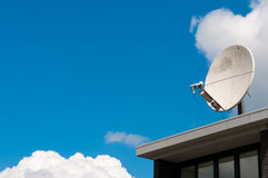 Une antenne parabolique blanche sur un toit Photos stock