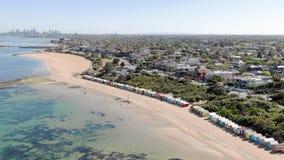 Une approche aérienne de Brighton Bathing Boxes avec la ville de Melbourne à l'arrière-plan, descente lente de la mer banque de vidéos